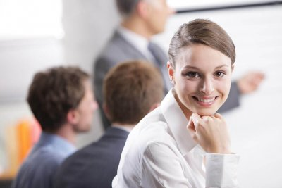 Young businesswoman smiling in a meeting with her colleagues in background